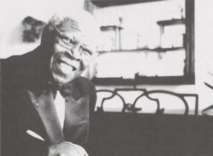 Black and white close up photograph of Al Dupree sitting in front of a piano. He wears a tuxedo jacket.