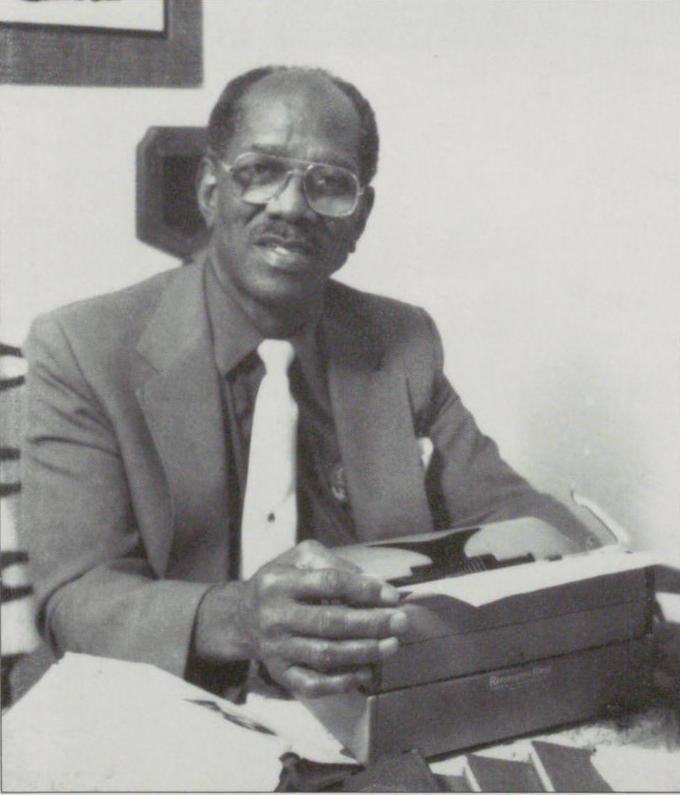 Black and white photograph of Clarence H. Gentry sitting at a desk with his hands on a typewriter.