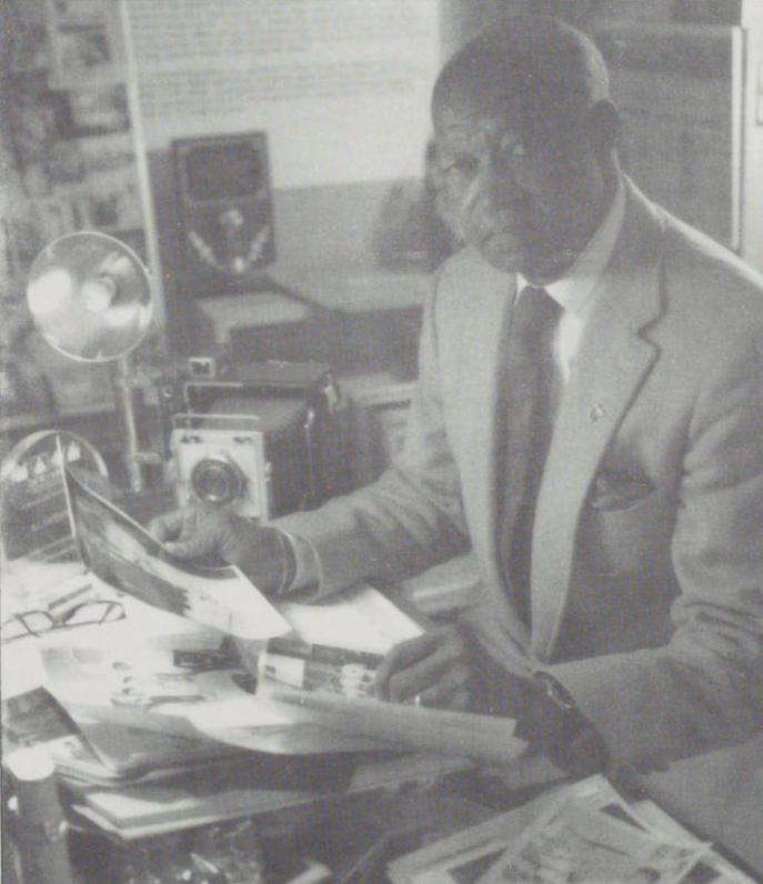 Black and white photograph of R.C. Hickman sitting at a desk covered with photographs and other materials. A large camera can be seen on the desk behind him.