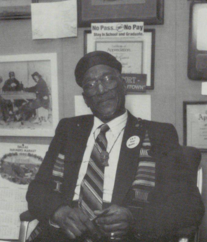 Black and white photograph of Albert Lipscomb sitting in front of a wall of framed photos and documents. He wears a beret, suit, and kente cloth style fabric sash tucked under his lapels.