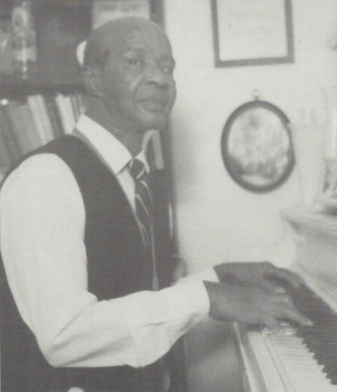 Black and white photo of Jimmy Smith sitting at a piano, with fingers on the keys.