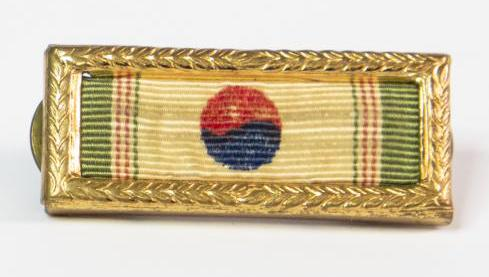A small rectangular ribbon tan in color but gren on the sides. In the middle is circle that is half red at the top and blue on the other half. The ribbon is inside a gold frame.