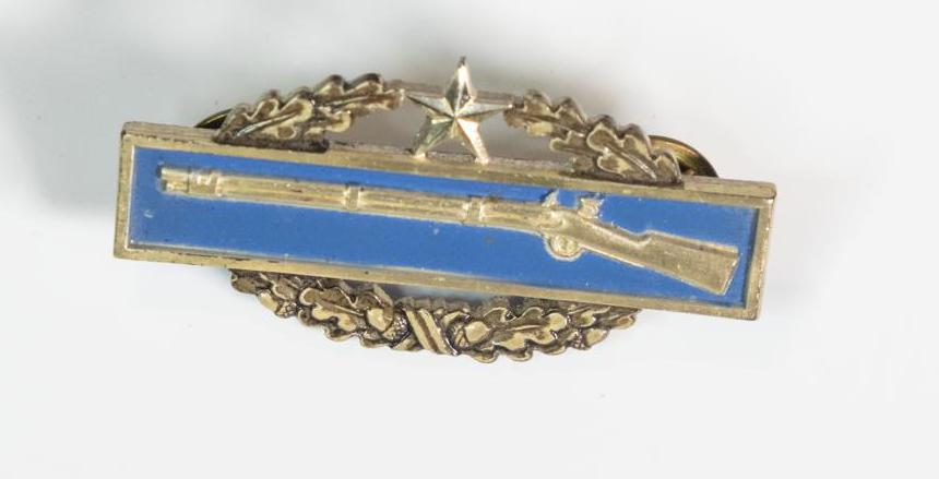 The image shows a blue rectangular shape, with the shape of a silver rifle  inside of it. It is also framed by silver. Under this part of the badge is  an oval wreath-like patterned that meets at the top with a small star in  the middle.