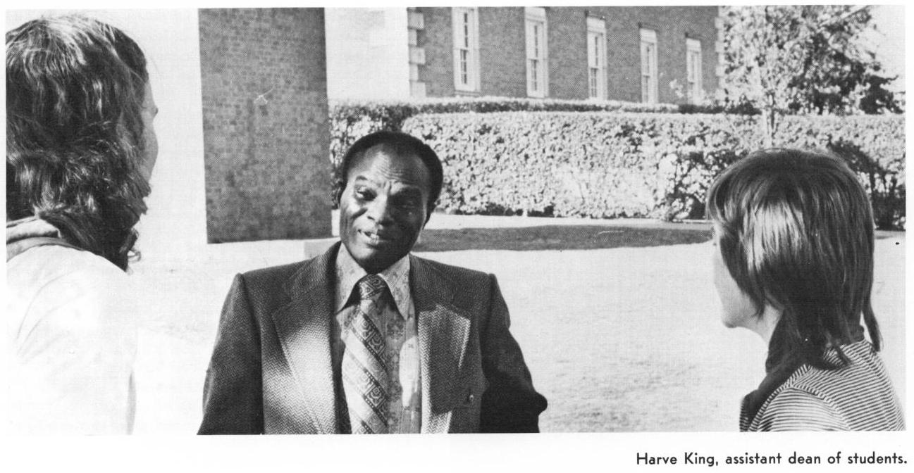 Black and white photo of an African American man in a suit, with two people standing by him talking to him. They are seen from the back. They all stand outside on campus. Under the picture is the main guys name, Harvey King and his title which is assistant dean of students.