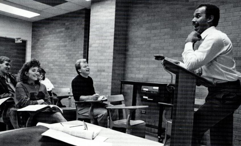 Black and white photo of a man standing behind a podium in a classroom, the desks filled with different students sitting in them. The room has a brick wall.
