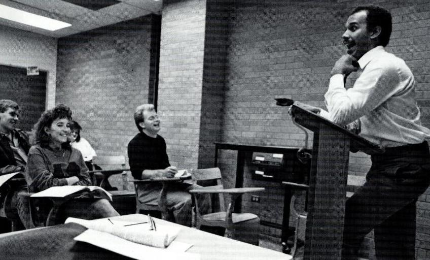 Black and white photo of a man standing behind a podium, laughing. By him are students sitting in desks inside a brick classroom.