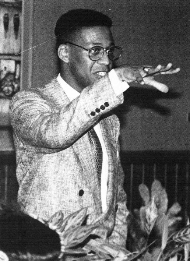 Black and white photo of an African American man in a shiny suit, wearing glasses and standing with his right arm extended in front of him palms down.